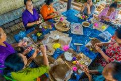 巴厘岛,印度尼西亚- 2017年3月08日:妇女印地安Sadhu面团为在Manmandir ghat的薄煎饼做准备在银行  库存照片