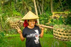巴厘岛,印度尼西亚- 2017年4月05日:妇女在戴米帽子和拿着用她的手棍子的米领域走 免版税库存图片