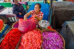 巴厘岛,印度尼西亚- 2017年3月08日:未认出的人在户外巴厘岛花市场上 巴厘语每日使用花 库存图片