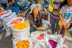 巴厘岛,印度尼西亚- 2017年3月08日:未认出的人在户外巴厘岛花市场上 巴厘语每日使用花 免版税库存图片