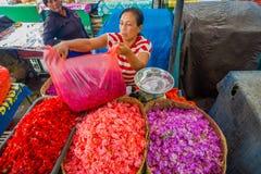 巴厘岛,印度尼西亚- 2017年3月08日:未认出的人在户外巴厘岛花市场上 巴厘语每日使用花 图库摄影