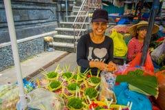 巴厘岛,印度尼西亚- 2017年3月08日:未认出的妇女做花的安排在箱子里面的由在a的叶子制成 免版税库存照片