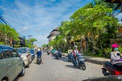 巴厘岛,印度尼西亚- 2017年4月05日:沿着走在ubud,巴厘岛的路的摩托车骑士 库存图片