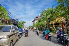 巴厘岛,印度尼西亚- 2017年4月05日:沿着走在ubud,巴厘岛的路的摩托车骑士 免版税库存照片