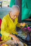 巴厘岛,印度尼西亚- 2017年3月08日:老妇人印地安Sadhu面团为在Manmandir ghat的薄煎饼做准备在银行 免版税库存照片