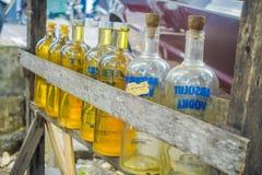 巴厘岛,印度尼西亚- 2017年3月08日:非法汽油汽油被卖在路,被回收的玻璃伏特加酒瓶的边 图库摄影