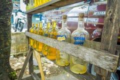 巴厘岛,印度尼西亚- 2017年3月08日:非法汽油汽油被卖在路,被回收的玻璃伏特加酒瓶的边 免版税图库摄影