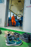 巴厘岛,印度尼西亚- 2017年4月05日:waitting在渡轮飞行员命令客舱外面的不同的鞋子有看法  免版税库存图片