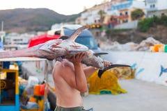 巴厘岛,海岛克利特,希腊, - 2016年6月30日:人是渔夫运载一条大鱼锯鲛 免版税库存图片