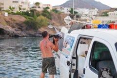 巴厘岛,海岛克利特,希腊, - 2016年6月30日:人是渔夫运载一条大鱼锯鲛 免版税图库摄影