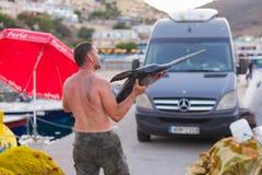 巴厘岛,海岛克利特,希腊, - 2016年6月30日:人是渔夫运载一条大鱼锯鲛 库存图片