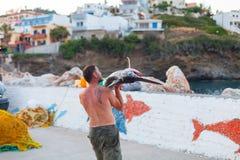 巴厘岛,海岛克利特,希腊, - 2016年6月30日:人是渔夫运载一条大鱼锯鲛 图库摄影