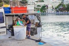 巴厘岛,海岛克利特,希腊, - 2016年6月30日:地方渔夫卸载从渔船的鱼捕获 免版税库存照片