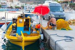 巴厘岛,海岛克利特,希腊, - 2016年6月30日:渔夫修理鱼网近的渔船 库存照片