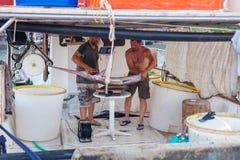 巴厘岛,海岛克利特,希腊, - 2016年6月30日:渔夫在渔的成功的鱼捕获以后称一条大鱼锯鲛 图库摄影