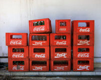 巴厘岛/印度尼西亚- 2016年9月09日:被堆积的条板箱在可口可乐红色塑料筐里面的瓶对白色墙壁 图库摄影