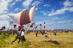 巴厘语少年发射一只大五颜六色的风筝 免版税库存照片