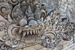巴厘语有传统卫兵邪魔头的寺庙墙壁 免版税库存照片