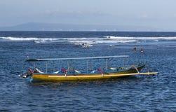 巴厘语渔夫去清早的抓住的岸 免版税库存照片