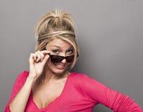 厚颜无耻年轻白肤金发偷看在她的太阳镜 库存照片