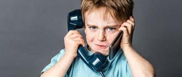 厚颜无耻的年轻男孩谈话在老电话和新的智能手机 免版税库存图片