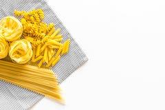 原始分类的意大利面食 意粉, fusilli, penne,在蓝色桌布的意大利细面条在白色背景顶视图拷贝 免版税库存照片