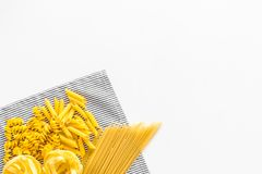 原始分类的意大利面食 意粉, fusilli, penne,在蓝色桌布的意大利细面条在白色背景顶视图拷贝 免版税库存图片