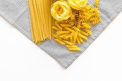 原始分类的意大利面食 意粉, fusilli, penne,在蓝色桌布的意大利细面条在白色背景顶视图拷贝 库存图片