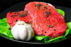原始牛肉的黑色的盘子 免版税库存图片