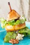 原始的方式供食与绿色叶子和青纹干酪a的梨沙拉 免版税库存图片