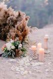 原始的以花和蜡烛的形式迷你的花束的婚礼花卉装饰仪式的 库存照片