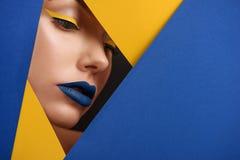 原始的beaty关闭女孩` s面孔由蓝色和黄色纸盒surronded 库存照片