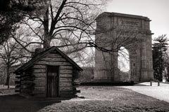 原木小屋和纪念曲拱在福奇谷公园 免版税图库摄影