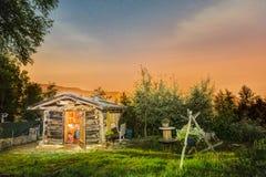 原木小屋在晚上 与满天星斗的天空的美丽的山小屋 免版税库存照片