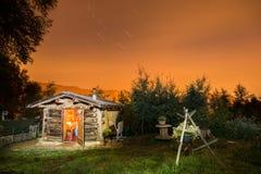 原木小屋在晚上 与满天星斗的天空的美丽的山小屋 免版税库存图片