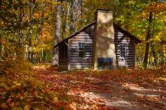 原木小屋在秋天森林 免版税库存照片