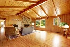 原木小屋房子内部 有壁炉和皮革的客厅 图库摄影