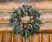 从原木小屋结构垂悬的土气秋天花圈 免版税库存照片