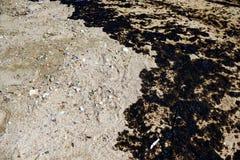 原油溢出纹理在沙子海滩从漏油事故,贴水Kosmas海湾,雅典,希腊, 2017年9月14日的 免版税库存图片