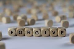原谅-与信件的立方体,与木立方体的标志 免版税库存照片