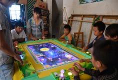 原阳,中国8月13日2013年:年轻男孩打一个电子游戏 图库摄影