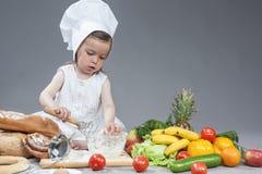 厨师一致的制造的食物的白种人女孩在厨房玻璃器皿 图库摄影