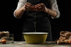 厨师与面团一起使用,打破鸡蛋和鞭子,focaccia、意大利面团、比萨或者面包的准备的 结冰  库存照片