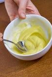 厨师为做乳酪蛋糕系列配套食物食谱用手鞭打在碗的黄色奶油 库存图片