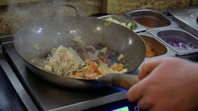 厨师倒大豆和teriyaki调味汁对乌龙面面条和油煎的菜在平底锅 股票录像