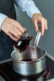 厨师倒酒入烹调的被仔细考虑的酒一个平底锅烹饪食谱的完全收藏 库存照片