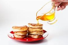 厨师倾倒在薄煎饼之上的甜糖浆 奶油被装载的饼干 图库摄影