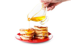 厨师倾倒在薄煎饼之上的甜糖浆 空白 免版税库存照片