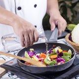 厨师倾吐的汤到烹调的平底锅 免版税库存图片
