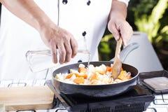 厨师倾吐的汤到烹调的日本猪肉咖喱平底锅 免版税库存图片